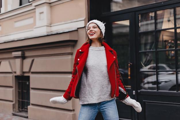 Garota legal em jeans, suéter cinza, casaco vermelho e chapéu de malha com luvas posando com sorriso na rua.