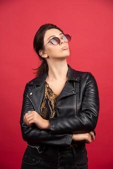 Garota legal em uma jaqueta de couro preta e óculos escuros parece severa e exigente.