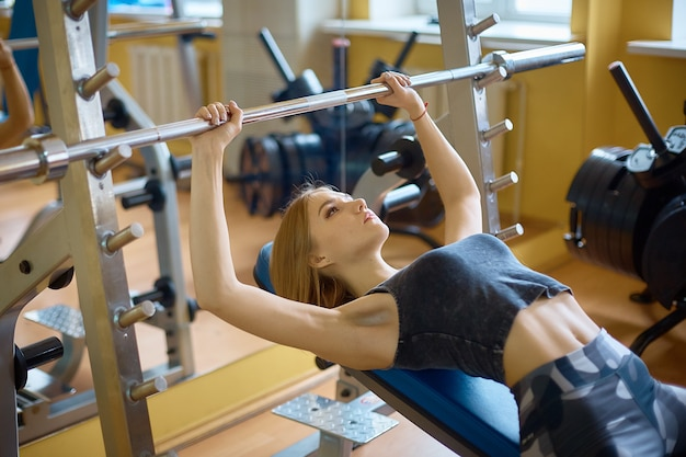 Garota legal, fazendo exercícios no simulador. modo de vida saudável, fazendo esportes