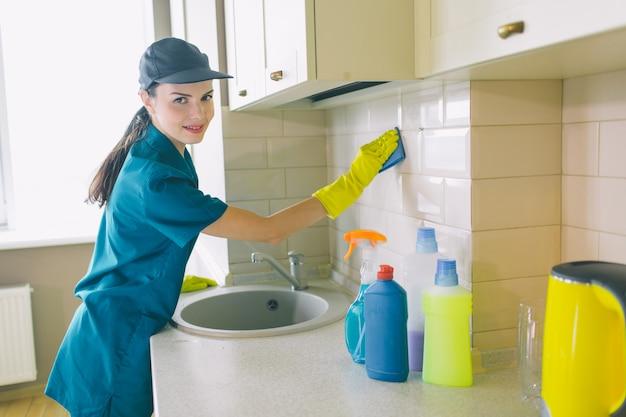 Garota legal fica e trabalha na cozinha. ela segura uma esponja azul. menina sorri um pouco. ela está feliz.