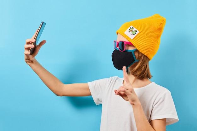 Garota legal hipster tirando foto no autorretrato do smartphone. adolescente de óculos usando chapéu de malha e máscara protetora, fazendo foto de selfie na parede azul.