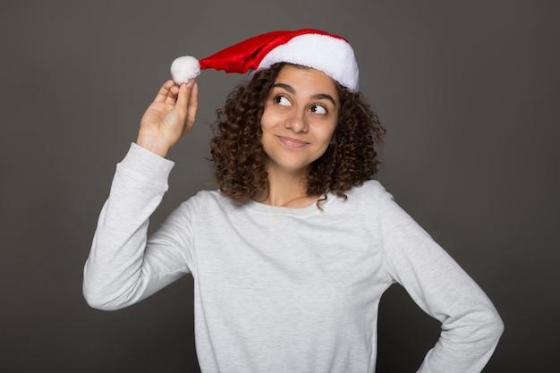 Garota legal indiana com chapéu de papai noel. natal. celebração de ano novo.