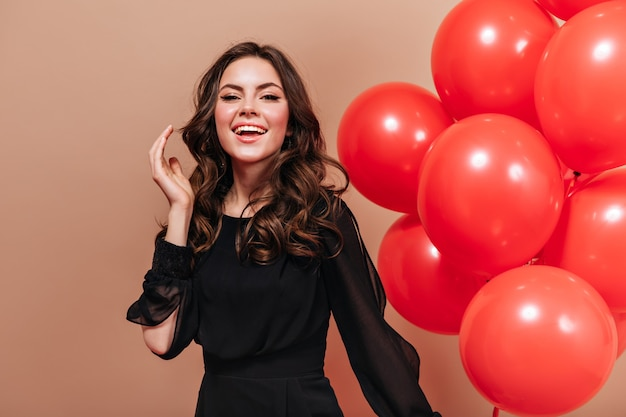 Garota legal na blusa de luz preta com sorriso olha para a câmera e posa em fundo bege com balões.
