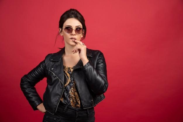 Garota legal na jaqueta de couro preta coloca o dedo no queixo e pensa.