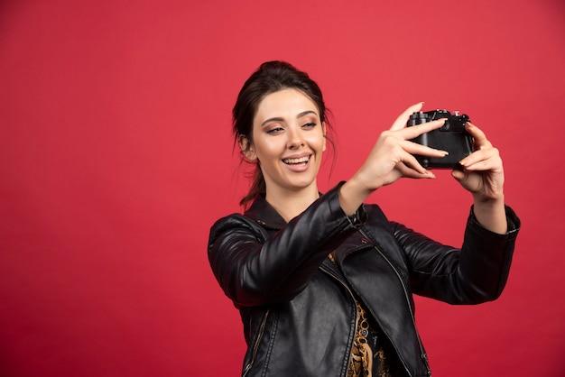 Garota legal na jaqueta de couro preta, segurando sua câmera profissional e tirando boas fotos.
