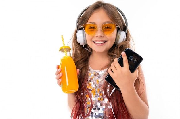 Garota legal no vestido brilhante e óculos de sol amarelos brilhantes, com grandes fones de ouvido brancos, ouvindo música e segurando preto smartphone e garrafa com suco de laranja isolado