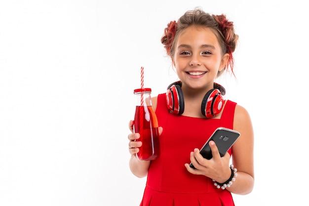 Garota legal no vestido vermelho com fones de ouvido grandes bebe suco isolado na parede branca