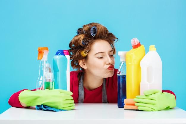 Garota legal senta-se atrás da mesa e ferramentas de limpeza, segurando-os