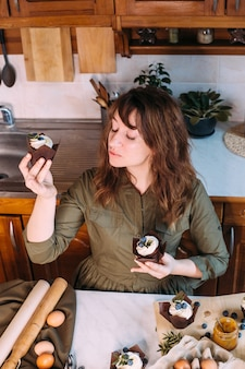 Garota legal sorri e detém cupcake e bata na cozinha de casa.