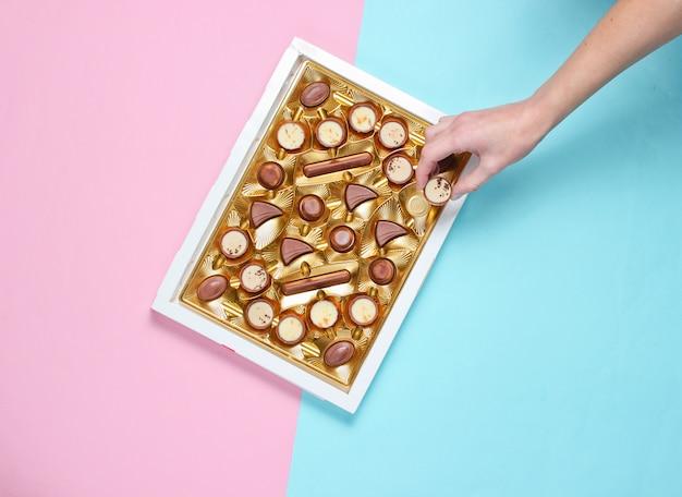 Garota leva um doce de chocolate de uma caixa de chocolates com uma bandeja dourada sobre fundo pastel rosa azul. vista superior, minimalismo