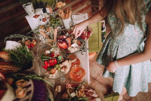 Garota leva uma fatia de queijo em uma mesa decorada com bolos