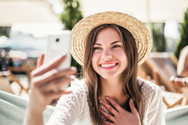 Garota ligando por videoconferência enquanto está sentada na praia no verão com um chapéu de palha está envergonhada e sorrindo