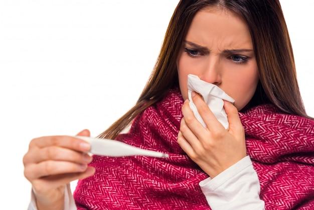 Garota limpa o nariz e olha para o termômetro.