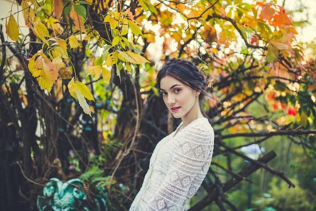 Garota linda blusa de renda branca em um parque de outono