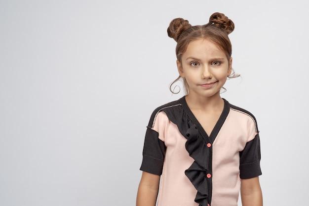 Garota linda camisola rosa levanta uma sobrancelha de surpresa, a criança não acredita em uma história fictícia, contou aos pais.