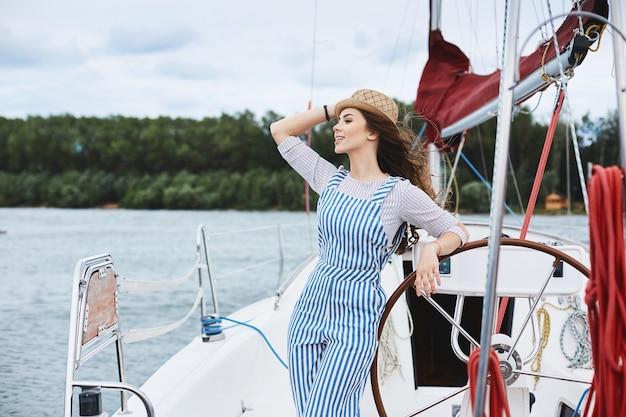 Garota linda e elegante modelo morena de macacão listrado branco e azul elegante e com um chapéu, segura seu chapéu da moda e posando em um iate no mar