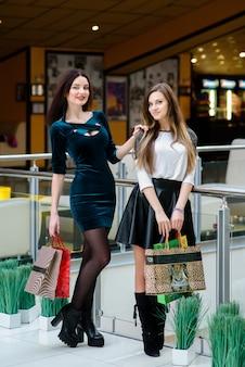 Garota linda e feliz fazendo compras no shopping.
