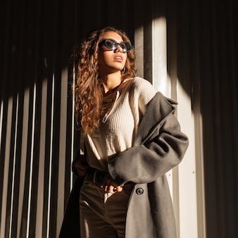 Garota linda e glamourosa na moda no estilo da moda outono com um casaco longo e um suéter com óculos de sol andando na rua sob a luz do sol