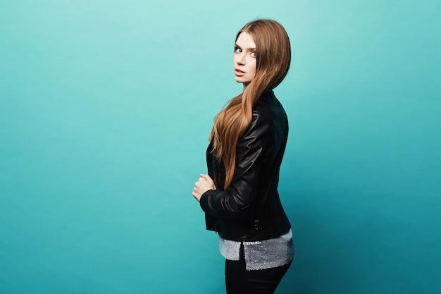 Garota linda e sexy modelo com cabelos longos na jaqueta de couro, posando sobre um azul claro no estúdio. vista lateral de uma jovem mulher bonita com maquiagem brilhante em uma roupa da moda. retrato recortado