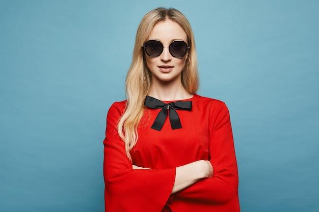 Garota linda e sexy modelo loiro com maquiagem suave em elegantes óculos de sol e no elegante vestido vermelho curto posando, isolado