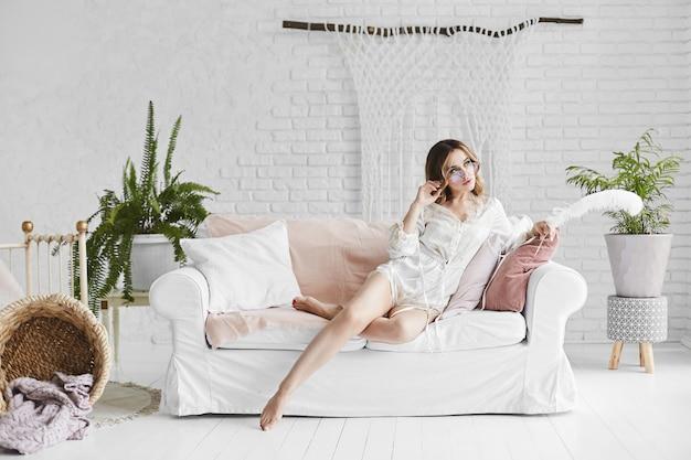 Garota linda e sexy pernas longas modelo loiro de óculos da moda e elegante pijama de cetim senta-se no sofá branco com almofadas e posando no interior branco no estilo moderno loft