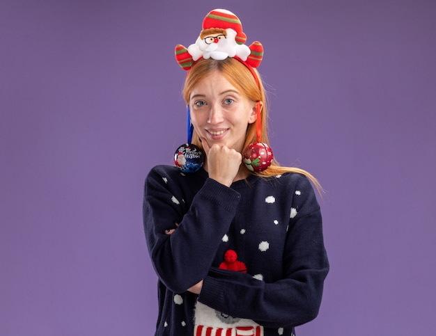 Garota linda e sorridente vestindo um suéter de natal com aro de cabelo de natal pendurado bolas de natal na orelha colocando a mão sob o queixo isolado na parede roxa
