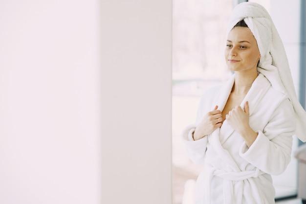 Garota linda em um roupão branco em casa