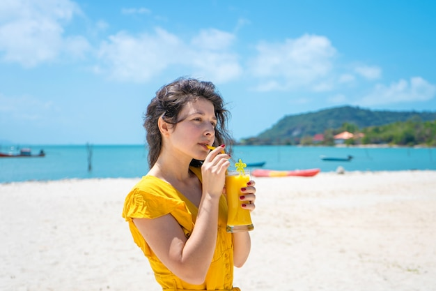 Garota linda em um vestido amarelo bebe manga fresca na praia de uma ilha paradisíaca. férias perfeitas.