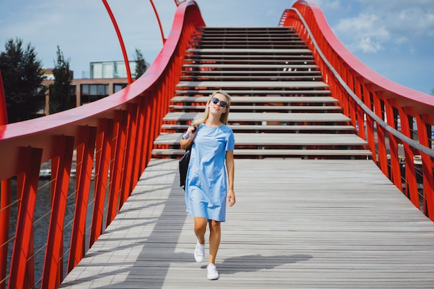 Garota linda em um vestido azul posando na ponte
