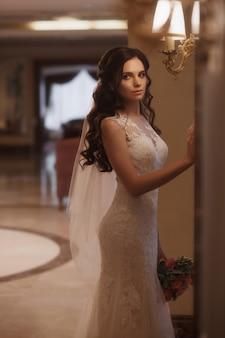 Garota linda em um vestido branco está se preparando para a cerimônia de casamento