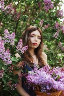 Garota linda em um vestido posando perto de lilases de bush