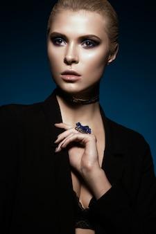 Garota linda em um vestido preto, cabelos lisos e maquiagem da moda. rosto de beleza glamour.