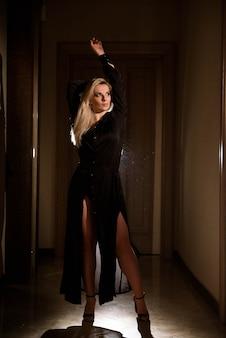 Garota linda em um vestido preto, posando na luz de fundo
