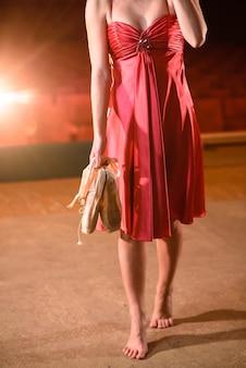 Garota linda em um vestido vermelho dançando no palco.