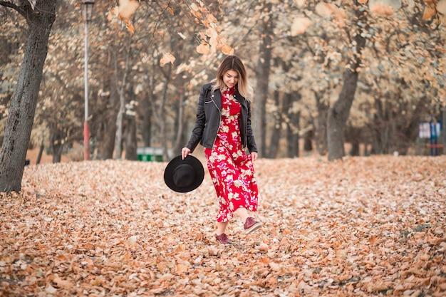 Garota linda em um vestido vermelho e jaqueta preta caminha no parque outono