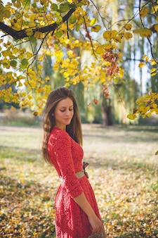 Garota linda em um vestido vermelho em um parque de outono