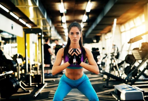 Garota linda jovem aptidão focada fazendo agachamentos com um kettlebell e olhando para a câmera no ginásio moderno.