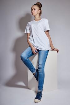 Garota linda jovem modelo em jeans azul e camiseta branca, posando no estúdio em branco