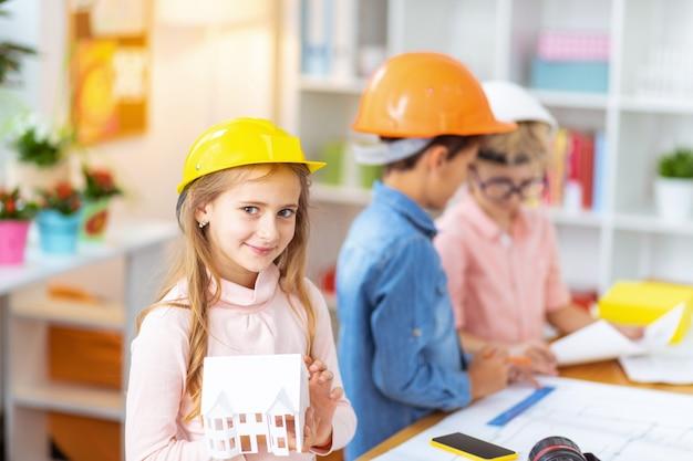 Garota linda. linda garota com um capacete animada ao estudar a modelagem de uma casa em pé perto de colegas de classe