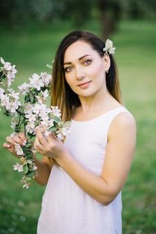 Garota linda no vestido branco com galho de árvore de maçã na primavera. maquiagem profissional, lindos olhos
