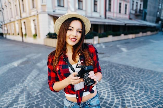 Garota linda turista com cabelo castanho, usando chapéu e camisa vermelha, segurando a câmera fotográfica no antigo fundo da cidade europeia e sorrindo, viajando.
