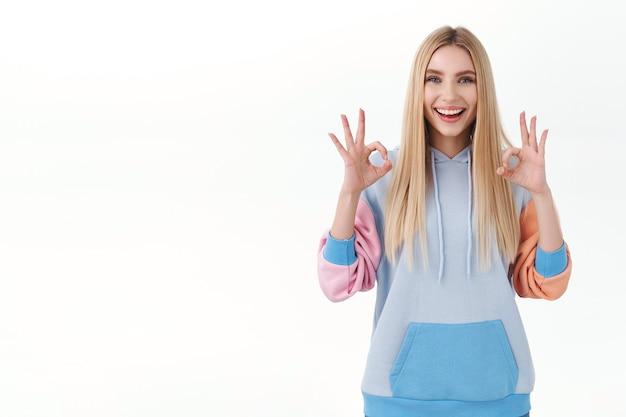 Garota loira alegre animada com sorriso radiante satisfeita com boa qualidade, mostrar gesto de ok rindo