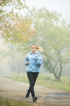 Garota loira ativa com capuz azul, leggins pretas e tênis correndo pelo caminho da floresta entre árvores com folhagem amarela em uma manhã de nevoeiro