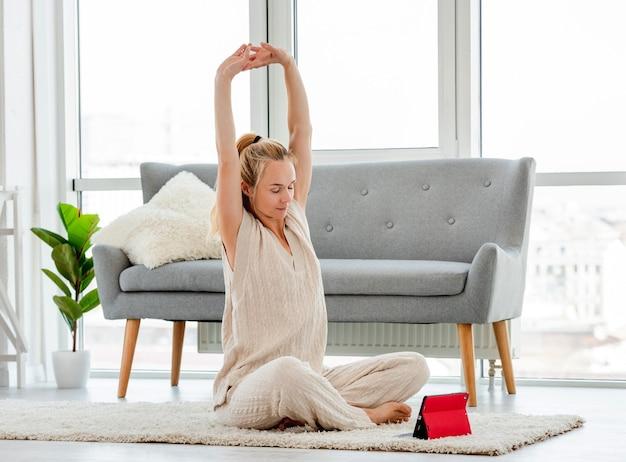 Garota loira atraente esticar suas costas durante a aula de ioga online no tablet. exercícios em casa em horário cobiçado