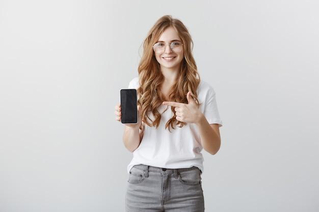 Garota loira atraente sorridente de óculos apontando o dedo para a tela do smartphone, mostrando o aplicativo