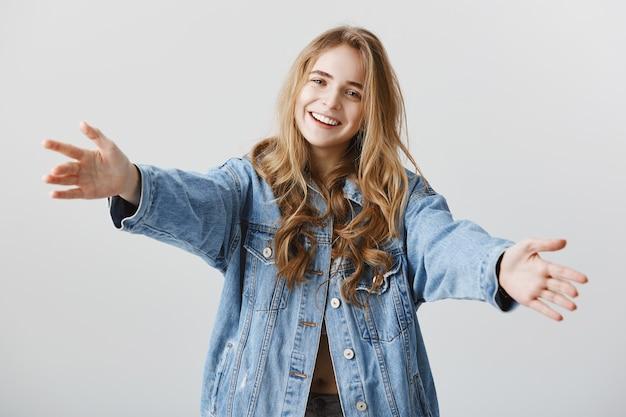 Garota loira atraente sorrindo feliz e espalhando as mãos para os lados para um abraço, abraçando ou pegando algo