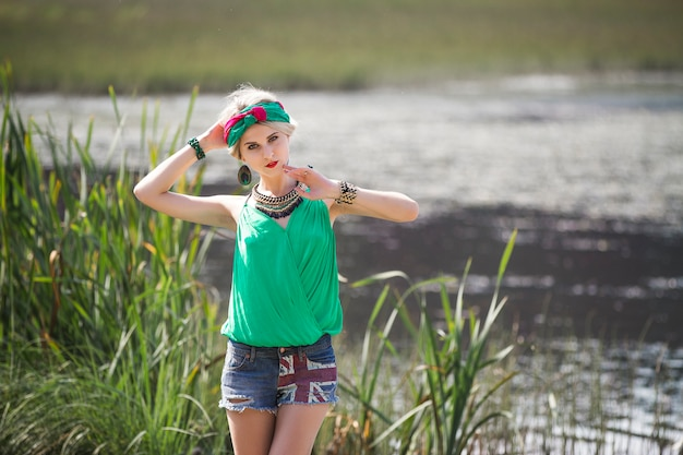 Garota loira bonita atraente em shorts e uma bandana caminha e posando no parque