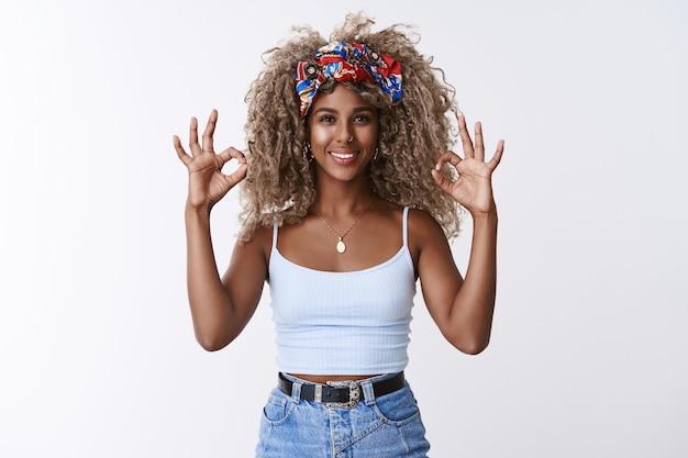 Garota loira bonita e otimista de cabelos cacheados com penteado afro, bandana, mostrar ok, ok sinal de confirmação e sorrindo, aceno em aceitação, gosto de ideia incrível, dê aprovação