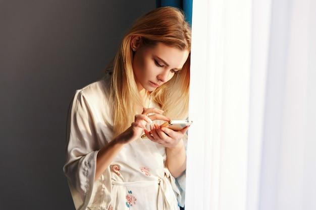 Garota loira checa seu telefone em pé antes da janela brilhante