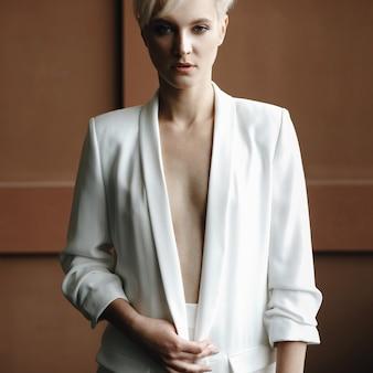 Garota loira com cabelo loiro curto coloca em terno branco no quarto